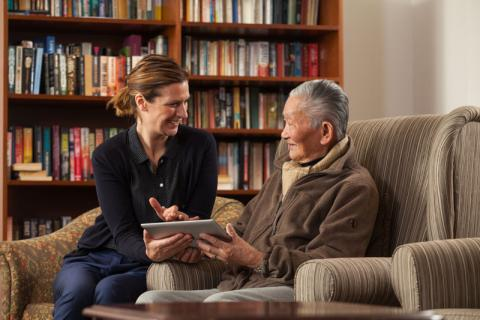 female sitting helping aged man with ipad